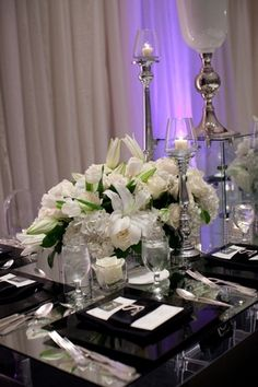 White lilies, tulips, roses, and hydrangeas arrangements on mirror top table, clear table