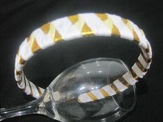 Vincha tejida con cintas en blanco y dorado.