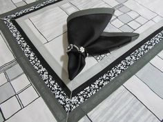 Toalha de mesa confeccionada em tecido de algodão, com estampa geométrica, com detalhes em estampa floral e acabamento em viés de algodão preto e cinza. Os guardanapos e porta-guardanapos são vendidos separadamente. R$ 140,00