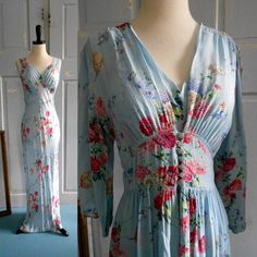 "A late 1940s to early 1950s nightgown and long jacket in light blue floral fabric that is a lightweight textured fabric and feels like crepe, cut on the bias and has a deep cut front neckline. Tiny little pleats above the bust.  Label: ""Tailored by Radcliffe."""