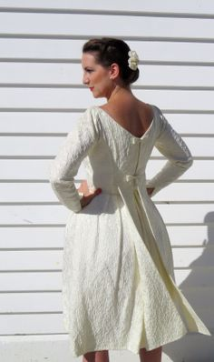 Gorgeous dress from the 1960s. Flattering slash neckline, below knee length and nipped in waist accentuated by a sweet bow. Long sleeves end in an elegant point. The back features two bows down the centre and two sashes falling from the waist to the hem. The fabric has a beautiful textured finish. A lovely one of a kind dress!