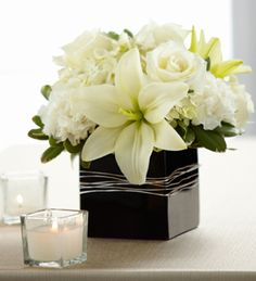 The FTD® State of Bliss™ Arrangement is an ideal centerpiece or accent piece for the wedding reception. White roses, Asiatic Lilies, carnations and hydrangea are offset by lush greens and arranged in a designer black ceramic cube vase to add to the elegan Lily Centerpieces, Wedding Centerpieces, Wedding Table, Wedding Bouquets, Wedding Decorations, Wedding Reception, Elegant Centerpieces, Vases, Wedding Ideas