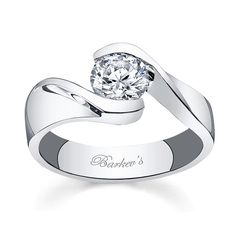 Bold contemporary styling makes a strong statement of confidence for the person who wears this diamond engagement ring.  A take on the vintage bypass ring of day gone by, this modern version has a channel set round diamond center and a stepped shank artfully curving down the shoulders with a bright mirror like polish for an added touch of glam.    Also available in yellow, 18k and Platinum.