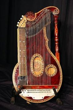 """I Love the given description:  """"Unidentified musical instrument"""". Dark red, ornate, lute like instrument - but with a seeming guitar fretboard on the side."""