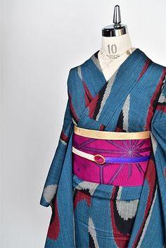 緑青をおびた光の加減で幻想的に色を変えるグレーの地に大胆に織り出された壺垂れ文様が印象的な御召の単着物です。