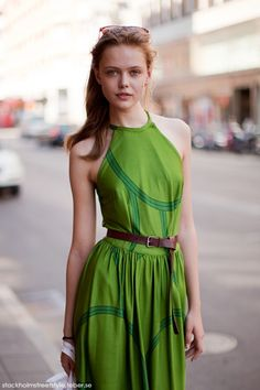 Chic combination of light green dress, brown belt, and sunglasses from Stockholm
