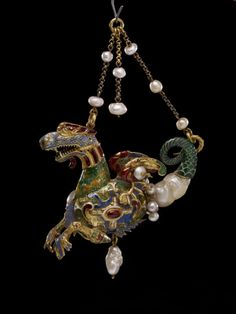 Pendant jewel; gold; form of sea-dragon; tail and one side of body formed of large baroque pearl, other side chased with cartouche and enamelled; colours are blue, green. lavender and ruby; wings are each set with pearls; plain suspension chain set with pearls; pearl pendant below. Spain. Late 16th century. Pearl, gold, enamel.