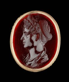 Intaglio. Portrait bust of Marciana, the elder sister of Trajan, in profile to the left. She has a lofty three-tiered coiffure. At the back of the head, the remaining hair has been twisted into a large nest of braids. This entire mass is backed by a diadem. She wears no jewelry, has a straight nose, and fleshy chin and cheek. She wears a cloak (stola). The identification as Marciana is based upon her unique three-tiered, scalloped hairstyle