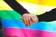 homosexual couple holding hands and rainbow flag