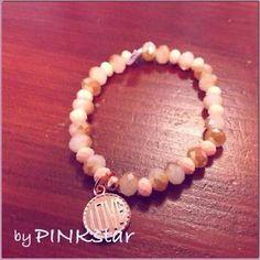Mooie elastieke roze en rosé gekleurde armband van facetkralen. Rosé love hanger.