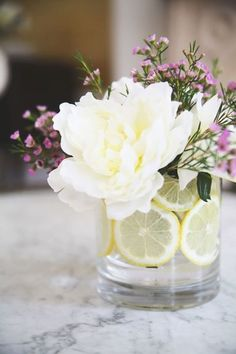 Citrus Floral Arrangement You'll need two vases for this bouquet! Start off by placing the smaller one inside the larger one, then slide slices of oranges or lemon inside the gap between them.
