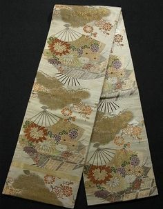 This graceful vintage maru obi has auspicious motif- 'kiku' (chrysanthemum), 'ume' (Japanese plum), 'matsu' (pine tree) are woven elaborately in fan pattern. Its tranquil background also has woven wave pattern.  The combination with gold threads and washy colored design has exceptionally gorgeous atmosphere.  Textile is exquisite silk and has soft and comfortable touch.