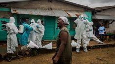 En esta imagen se aprecia a miembros de  la Cruz Roja vestidos con ropa de protección antes de retirar el cuerpo  de una víctima del virus del ébola en el centro de Monrovia, Liberia