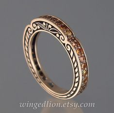 This breathtaking wedding band was designed by the artist and jewelry designer Sergey Zhiboedov. It will be made to order in 14k rose gold in the size specified by the customer.  The band is designed to be worn with one of our most popular ring designs - the Caryatid ring. Still, the band can stand on its own as a refreshing alternative to an eternity band.  The CARYATID bands sides are adorned with scroll carvings. On the top, there are 28 genuine 1.6mm orange sapphires (VVS quality, total…