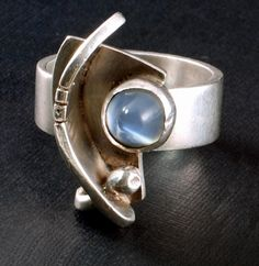 """Fabulous sterling ring by Ed Wiener with beautiful bullet-shaped cabochon moonstone with a blue tone; about size 6-1/4; top is approximately 1"""" long x 1/2"""" wide and the band is about 1/4"""" wide. It is marked: """"ED WIENER, STERLING;"""" small ball has dents which are most likely original; bezel also has some indentations, but they do not detract from the beauty of this ring.  $650.00 (item #SMMW001)"""