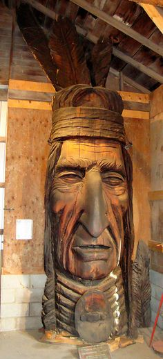 This statue is located inside the historic fire station of the Centennial Village of the Brown County Fairgrounds in Aberdeen, South Dakota. It is dedicated to the Native Americans of the Mount Rushmore State. Carved in 1981, it is one of a series of large wooden carvings called the Whispering Giants by sculptor Peter Toth of Hungary.