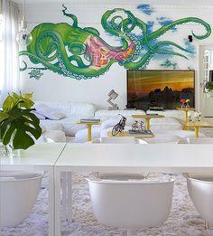 Sala de jantar | A partir do escritório, vê-se o ambiente com mesa Dart e cadeiras Strip, ambas da Poliform. Pendentes E27, da Micasa. A foto, ao fundo, é de Tuca Reinés, e o grafite, criado por Binho Ribeiro (Foto: Tuca Reinés e Denilson Machado/ MCA Estúdio)