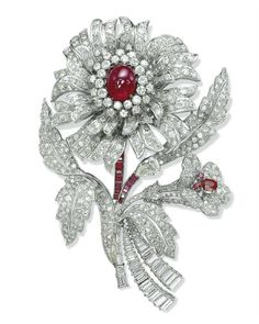 A RUBY AND DIAMOND BROOCH. Designed as a stylized flower with pavé-set diamond petals and leaves centering upon a cabochon ruby pistil mounted en tremblant, to the calibré-cut ruby and baguette-cut diamond stem, the smaller flower also with a ruby pistil, mounted in platinum, 11.0 cm.