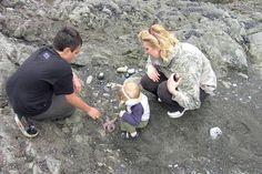 Riley, Brandon, and Valerie looking at a star fish at Rialto Beach.