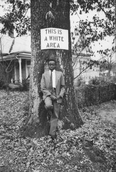 Kenyan student Philip Maundu of Morehouse College, stands underneath a racially discriminate real estate sign. Photographer: Ted Russell