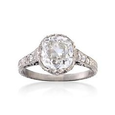 Vintage 2.10 ct. t.w. diamond engagement ring with magnificent 1.80 carat cushion-cut diamond. An additional .30 ct. t.w. of diamonds adorn the uniquely designed band. Textured platinum ring.