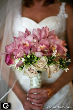 A bridal bouquet composed of light pink Cymbidium orchids, and a layer of Bouvardia and Sahara roses with a white satin ribbon wrap.