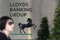 LONDON – Britain s state-rescued Lloyds Banking Group announced Friday that net profits sank by a fifth in the first quarter, after taking a charge against the disposal of its TSB retail division.