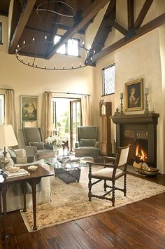 Dramatic stained trusses, a circular iron chandelier. Love the leaded glass window pattern echoed in the fireplace surround and coffee table.