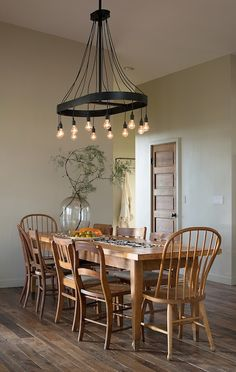 Love this country rustic look. The light fixture, plank floors, table...even the classic wooden door.