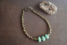 """This minimalist bracelet is called """"Fascinating Fox""""  Vintage Japanese fluted sea foam green glass flower rondelles paired with gorgeous brass nuggets. If you would like to know more about this piece please feel free to visit my etsy shop; arcanememory.etsy.com"""