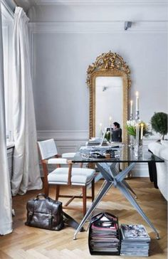 A chic white home office with a gold mirror