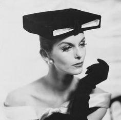 Model wearing 'academic' box hat, black gloves, and pearl earrings.