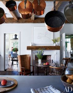 Vintage copper pots shimmer in the kitchen of a Martha's Vineyard, Massachusetts, home decorated by Mark Cunningham, where a Kelly lithograph overlooks a 19th-century tavern table and two antique chairs.