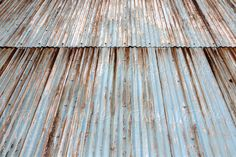 Old corrugated steel sheets on the outside of a building. Paint flaking and rust
