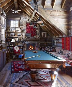In the billiard room, a 1920s Arts and Crafts light fixture hangs above a circa-1890 billiard table, the custom-made banquette is upholstered in a suede by Ralph Lauren Home, and the pillows are covered in remnants from vintage Navajo textiles.    - ELLEDecor.com