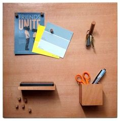 The Smorgas Board is a wooden magnetic bulletin board with wooden attachments that let you store everything: Pegs for your pictures and notes, hooks for your