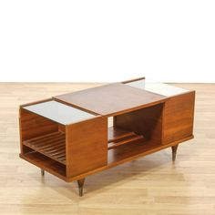 This mid century modern coffee table is featured in a solid wood with a glossy teak finish. This unique coffee table has 2 glass tier shelf inserts, 3 interior cabinet cubbies and tapered feet. Eye catching piece with tons of storage for books and magazines! #americantraditional #tables #coffeetable #sandiegovintage #vintagefurniture