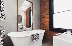 Blended modern rustic design with red exposed brick and white wall tile.