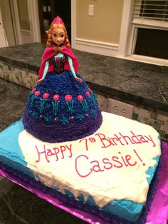 """A Disney Frozen themed birthday cake with an Anna doll cake. 1/2 chocolate sheet cake with white chocolate ganache for the """"ice""""."""