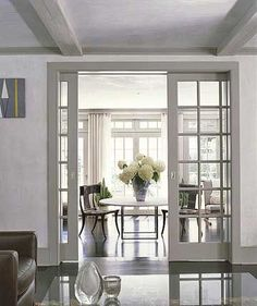 Paned-glass Pocket Doors What's more convenient than doors that disappear when you don't need them? That's the beauty of pocket doors. These paned-glass interior doors mimic the home's exterior windows. Leading from the living room, the pocket doors open on to an airy sunroom with casual dining and sitting space. More