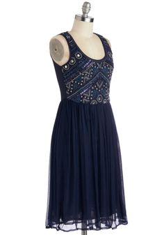 Sleeveless lined navy tank dress with scoop neck and heavily beaded bodice front in purple, silver, gold, navy, and rhinestones; sheer bodice back; fingertip-length skirt pleated to empire waist; and side hidden zipper. Extend beading to back! 100% polyester, from ModCloth, $104.99