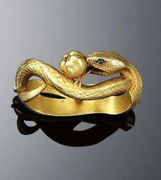 GOLD CRAVAT PIN, FRÉDÉRIC BOUCHERON, 1890S. Designed as a textured gold serpent with cabochon emerald eyes, encircling an apple, signed F. Boucheron, French assay marks.