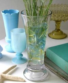Sea glass in water in a vase, add sea grass or flowers. Looks good enough to drink. Cute turquoise cup and vase, too.
