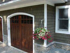 green stained cedar shingles. wood garage door.