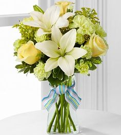 The FTD Boy-Oh-Boy Bouquet employs roses and Asiatic lilies to send your bright and sunny congratulations on the birth of their new baby boy! Yellow roses and carnations are brought together with pale green mini carnations, white Asiatic lilies, yellow solidago and lush greens exquisitely arranged in a clear glass gathered square vase.  at $47.90  http://www.bboescape.com/products/buy/179/say-it-with-flowers/FTD-Boy-Oh-Boy-Bouquet