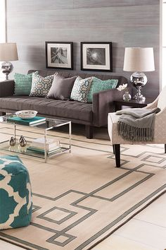 Grays and teals work together to create a tranquil living room grounded by an Alfresco Collection rug. Surya pillows, poufs, lighting, and a throw complete the look.