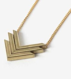 Minimalist in shape, this long necklace features a stacked pendant in a chevron shape. The golden brass v's are handmade in squared stock, combined into a single pendant and suspended from a long length of gold plated chain. Its simple design layers well with other charms and pendants or adds that finishing touch to a basic tee.