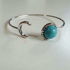 """Cresent moon Turquoise adjustable bracelet This lovely adjustable wire bangle bracelet has a silver cresent moon on one side and a lovely plastic turquoise circle on the other side. This is brand new and unused and 7 1/2"""" in the picture. Super cute and great with your favorite shirt and jeans. Jewelry Bracelets"""