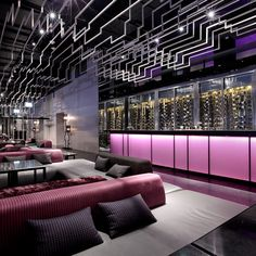 Steel light fixtures descending in stages from the ceiling and staircase hand-rails forming terraced access points give this place a video game feel lent a sophisticated sheen from rich magenta and purple features. It's hip to be square...