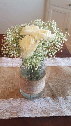 3 white carnations with babysbreath in a burlap lace jar Carnation Centerpieces, Mason Jar Flower Arrangements, Burlap Centerpieces, Mason Jar Flowers, Mason Jar Centerpieces, Centrepieces, Centerpiece Decorations, Wedding Centerpieces, Carnation Wedding